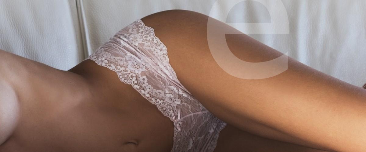 Emma escort en barcelona tumbada en un sofá con unas braguitas de encaje de lencería